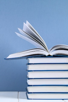 A stack of books on blue background. one hidden book on top of the pile.