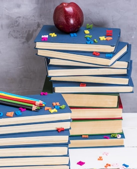Stack of books in the blue cover, multicolored wooden pencils