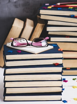 Stack of books in a blue cover, pink glasses on top