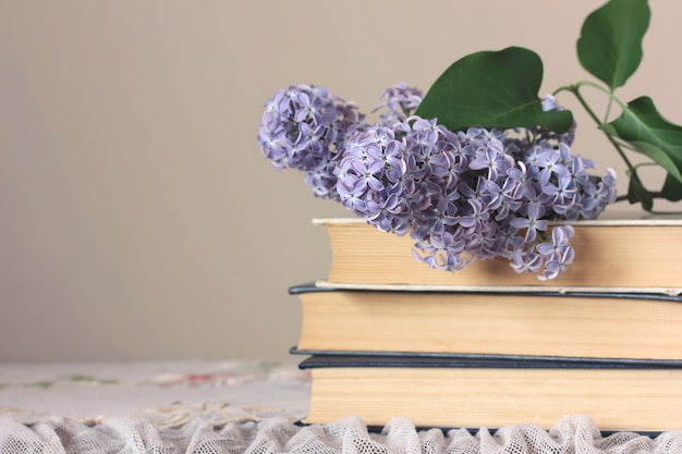 Stack of books and a branch of blooming lilac on the table on a board background.