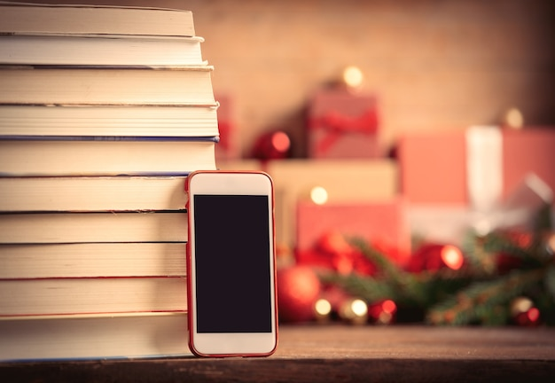 Stack of books and cell phone with christmas gifts on background