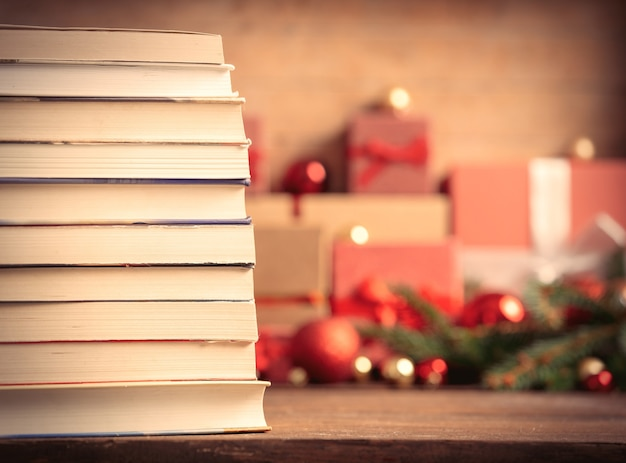 Stack of books and christmas gifts on background