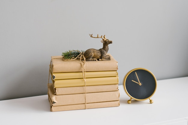 A stack of books in crane paper, tied with twine, they is a statuette of a sitting deer standing next to a desk clock