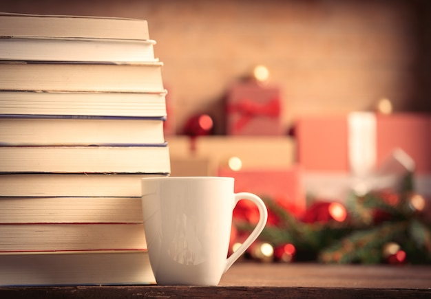 Stack of books and cup of coffee with christmas gifts on background
