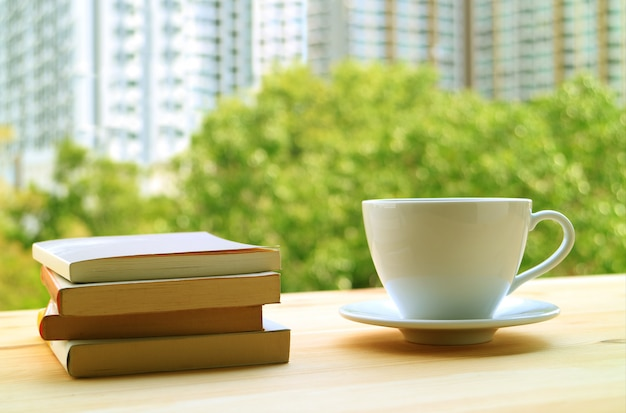 Stack of books and a cup of hot drinks on table by the window with green foliage and high building
