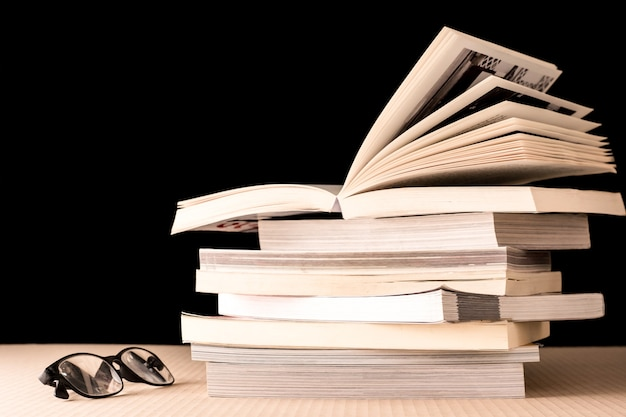 Stack of books and eyeglasses on wooden table, black background