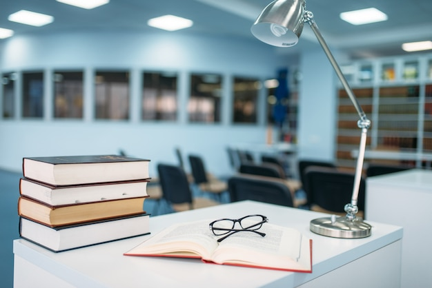 Stack of books and glasses on table in library