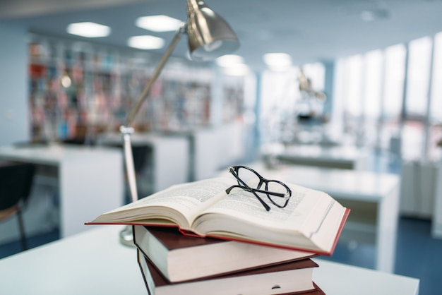Stack of books and glasses on the table in university library, nobody. knowledge depository, education concept