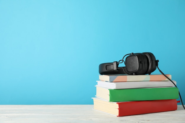 Stack of books and headphones on wooden table, space for text