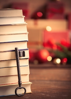 Stack of books and key with christmas gifts on background