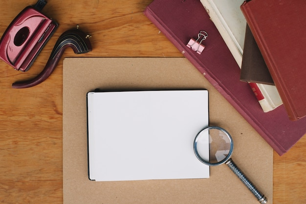 Pila di libri e lente d'ingrandimento vicino notebook