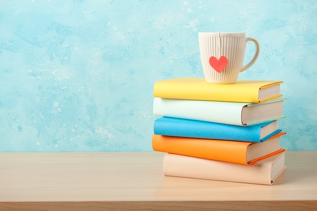 Stack of books and mug on wooden table