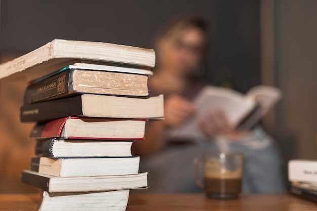 Stack of books near reading woman and coffee