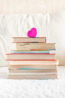 Stack of books and pink heart on the white bed