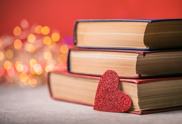 Stack of books and red heart. romantic background with the book