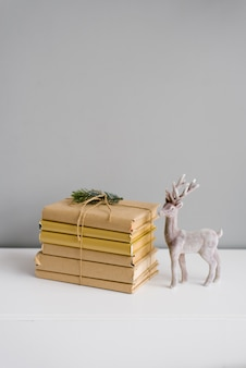 A stack of books and a sprig of spruce and next to a statuette of a deer