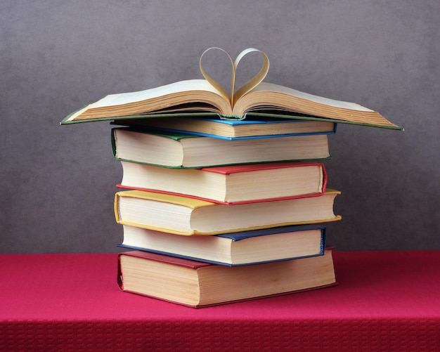 Stack of books on the table with a red tablecloth.