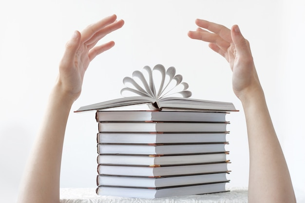 A stack of books on top of an open book and two hands over the books. the concept of learning, school, reading, literature