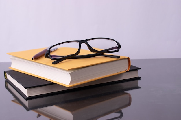 Stack of books on white background with glasses. world book day concept.