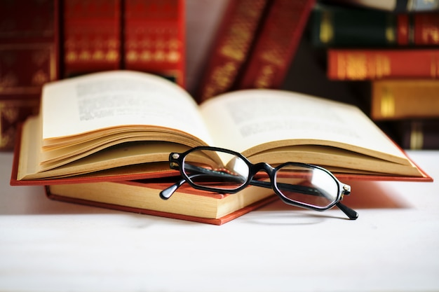 Stack of books with black men's glasses placed on the open book in library or on the white table