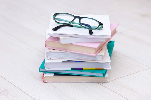 Stack of books with glasses on top. concept cause of farsightedness, myopia.