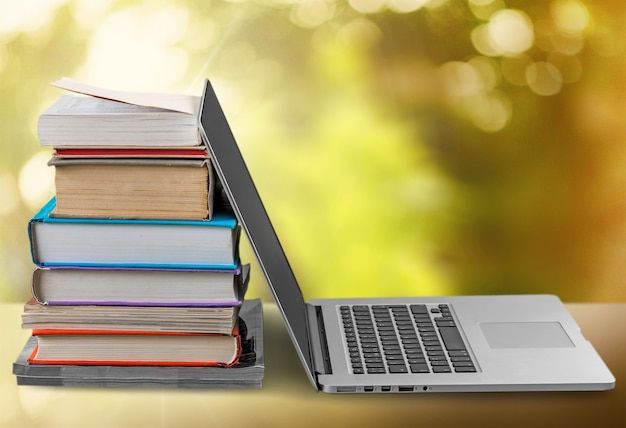Stack of books with laptop on table