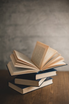 Stack of books on a wooden table and on gray concrete wall background