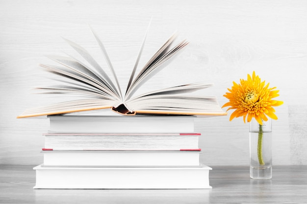 Stack of books and a yellow flower in a vase.