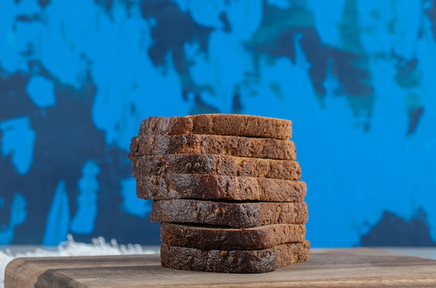 Stack of bread slices on wooden board.