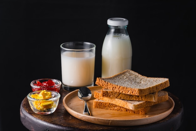 Stack of bread with milk, butter and strawberry jam on circular wooden table