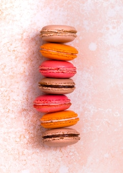 Stack of brown; orange and pink macaroons on textured weathered backdrop