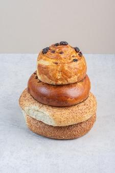 Pila di panini e bagel su sfondo grigio. foto di alta qualità