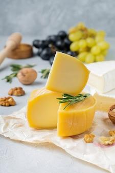 灰色の明るいコンクリートまたは石の背景にブドウ、クルミ、バジルとカマンベールチーズを積み重ねる
