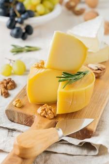 Сложите сыр камамбер с виноградом, грецкими орехами и базиликом на серой светлой бетонной поверхности
