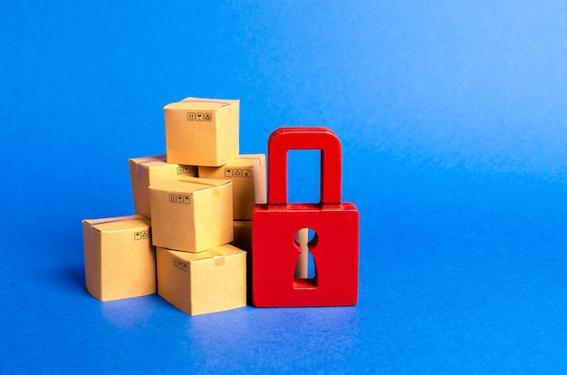 A stack of cardboard boxes and a red padlock concept of insurance purchases