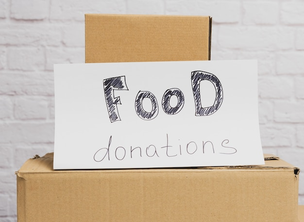 Stack of cardboard boxes and white sheet of paper with inscription food donation on white brick wall background