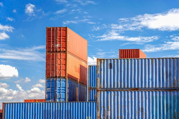 Stack of cargo containers in an intermodal yard with blue sky