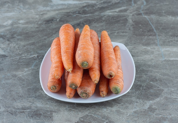 A stack of carrots in the plate , on the marble table.