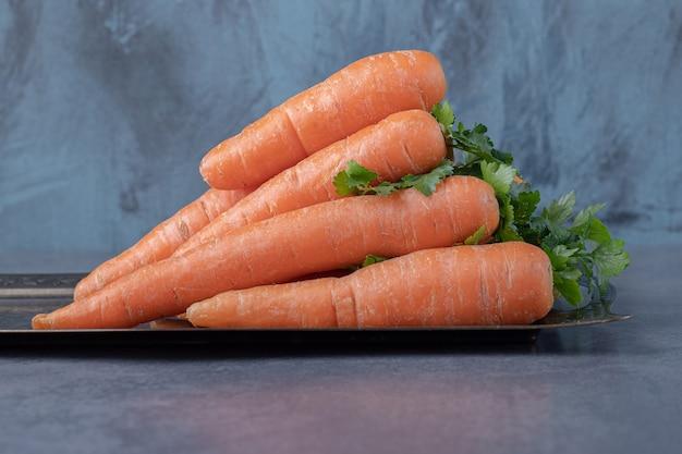 Una pila di carote sul vassoio, sulla superficie di marmo.