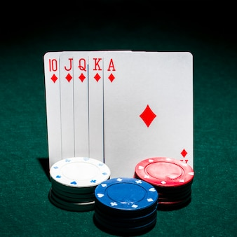 Stack of casino chips in front of royal flush playing card on poker table