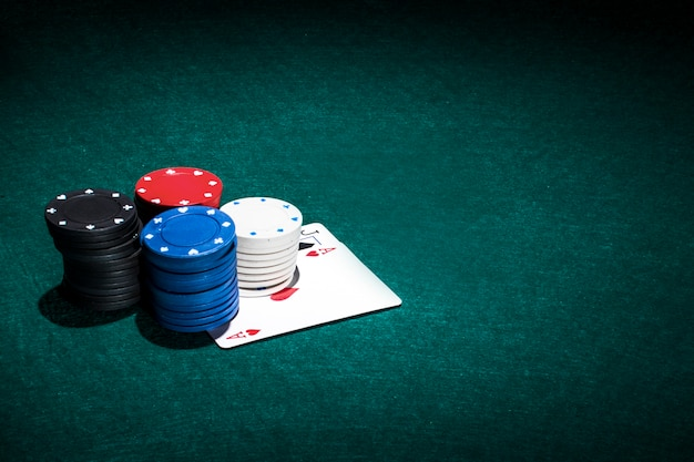 Stack of casino chips and poker card on green table