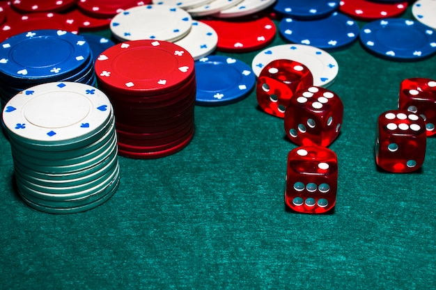 Stack of casino chips and red dices on green poker table