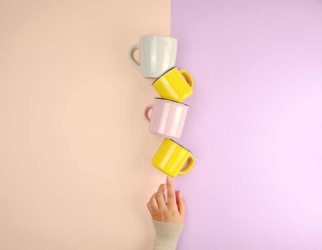 Stack ceramic cups are supported by a female hand