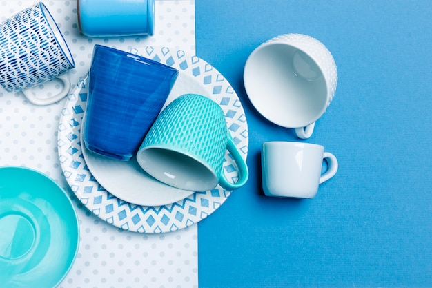 A stack of ceramic plates, glasses, mugs. simple design, close-up top view. place for your text.