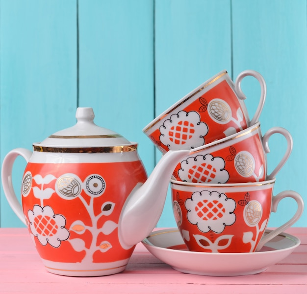 A stack of ceramic retro cups with red patterns and teapot on a pink wooden table