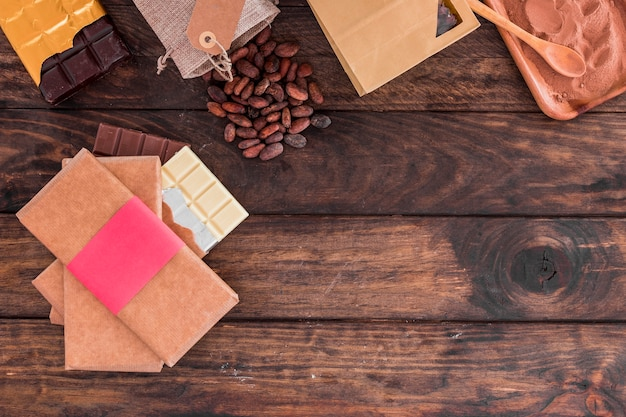 Stack of chocolate bars, cocoa beans and powder on wooden desk