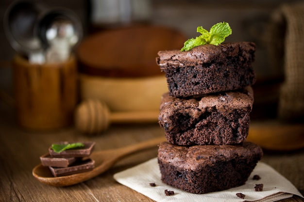 Stack of chocolate brownies on wooden background with mint leaf on top, homemade bakery