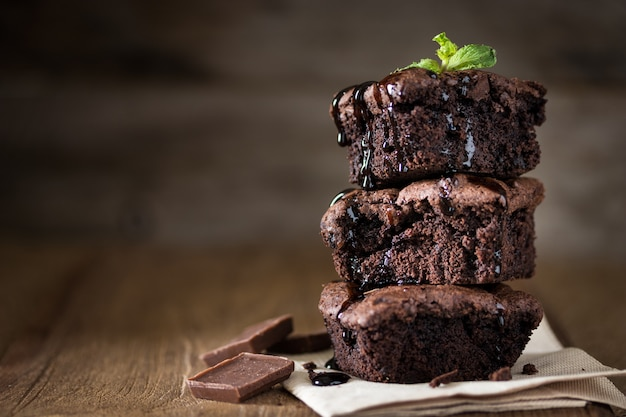 A stack of chocolate brownies on wooden background with mint leaf on top