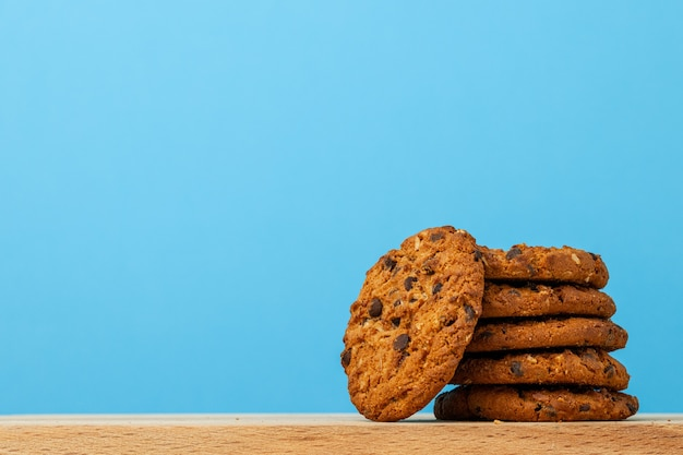 Stack of chocolate chip cookies against blue background