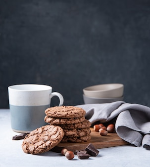A stack of chocolate chip cookies with chocolate chips and  nuts with cup of tea  on a light table. front view and copy space